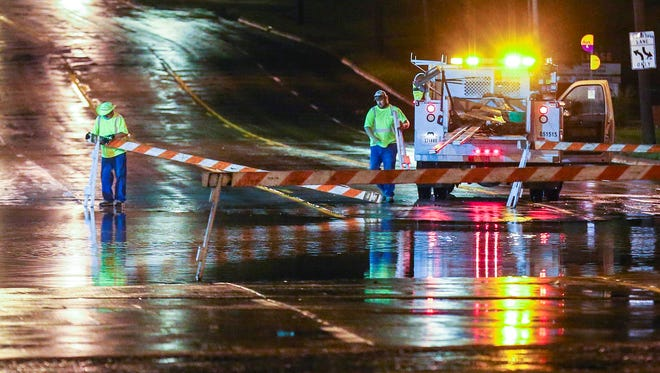 City workers close Grand Avenue at 62nd Street in West Des Moines Thursday, June 25, 2015, after heavy rain caused flash flooding.