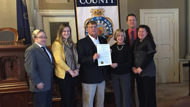 The Adams County Board of Commissioners pose with leaders of the Adams County Children's Advocacy Center after proclaiming Oct. 26, 2016 as the organization's 10th anniversary.