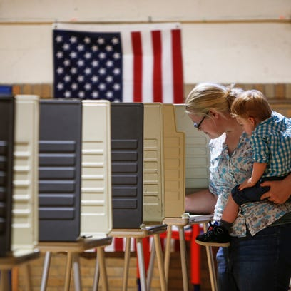 Rachel Beyer casts her vote early Tuesday evening,