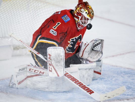 Calgary Flames goalie Brian Elliott blocks a shot by the Minnesota Wild during the second period of an NHL hockey game Wednesday, Feb. 1, 2017, in Calgary, Alberta. (Jeff McIntosh/The Canadian Press via AP)