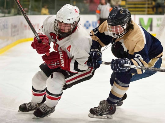 Champlain Valley's Kaleb Godbout, left, and Essex's Brendan Gleason close in on the puck in the Division I state championship game last season.