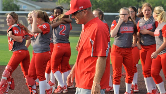 A smiling Heath Gibson leads his celebrating Hermleigh softball team to the outfield for team pictures after winning Thursday's regional final at ACU.