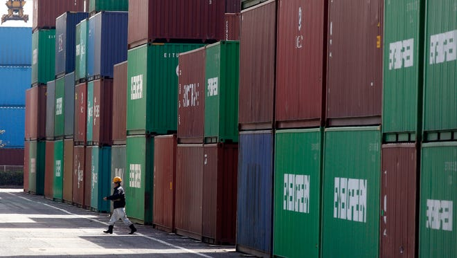A port worker walks through the piled containers in Tokyo.