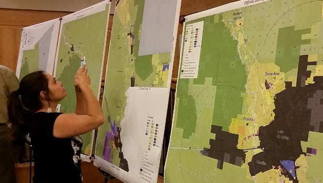 Kat Aguilar, who lives in the Sleep Farms Subdivision of Vado, photographs a map during an August meeting at the county headquarters in Las Cruces about Doña Ana County's proposed land-use overhaul. The proposal, known as the Unified Development Code, is scheduled for two days of hearings before the Planning & Zoning Commission on Oct. 11 and 13, officials have said.