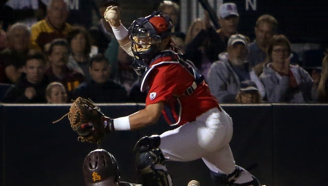 Arizona catcher Cesar Salazar (12) shows off the ball after tagging Arizona State runner Andrew Shaps (16) out on a tag from third on a fly ball to right field foul territory to end  the top of the third inning of their game at Hi Corbett Field, Tuesday, April 4, 2017, Tucson, Ariz.