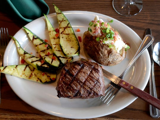 The baseball cut of prime top sirloin with a loaded baked potato and char-grilled zucchini at Rudy's Restaurant at Salem Golf Club on Wednesday, Sept. 17, 2014.