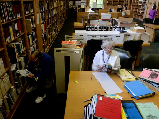 Sue Bell, right, and Susan Niggli, both volunteers with the Willamette Valley Genealogical Society, sorts through materials in the reference room at the Oregon State Library in Salem on Friday, Oct. 24, 2014. The WVGS is working to move all its resources to the Salem Public Library, a process that will take months.