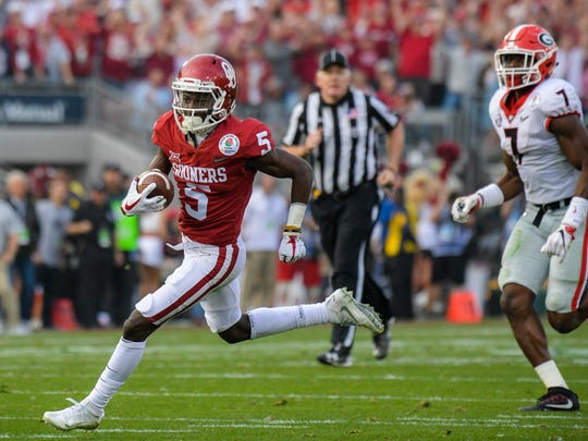 Oklahoma Sooners wide receiver Marquise Brown (5) carries the ball against the Georgia Bulldogs in the 2018 Rose Bowl college football playoff semifinal game at Rose Bowl Stadium. Waynesboro's Jim Hyson, an umpire in the game, can be seen in the background.
