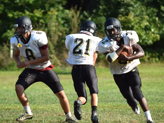 Dylan Thompson, right, heads upfield after taking a handoff from Dylan Rankin, left, while Josh Reed carries out his fake during practice on Tuesday, Aug. 22, 2017, at Buffalo Gap High School in Buffalo Gap, Va.