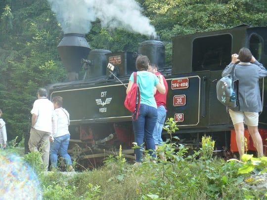 Tourists prepare to take the steam-powered railway into the Carpathian mountains near Viseu de Sus, Romania.