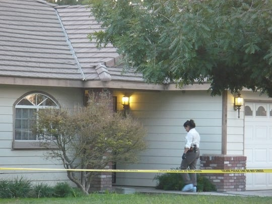 A Tulare police detective walks into a home in the