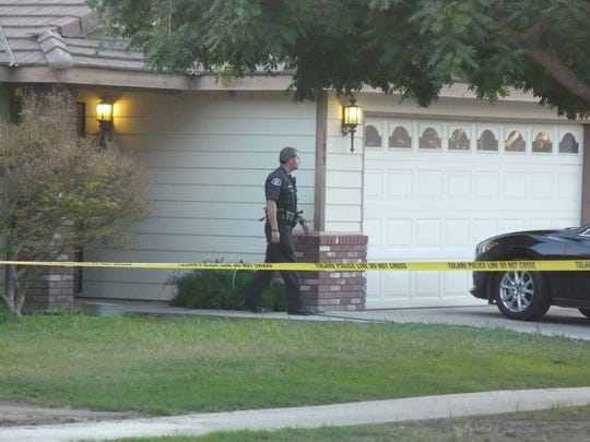 A Tulare police officer walks out of a home in the