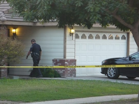 A Tulare Police Officer walks into a house in the 200