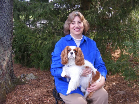 Hunterdon County-based author Loren Spiotta-DiMare is shown with local Cavalier King Charles spaniel and pet therapy dog, Carson.