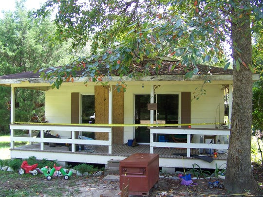 Crime scene tape marks the home on Jim Platt Road near Citronelle, Ala., Sunday, Aug. 21, 2016, where authorities said five people were killed on Saturday. Police said that Derrick Dearman, 27, of Leakesville, Miss., has been taken into custody in connection with the murders.