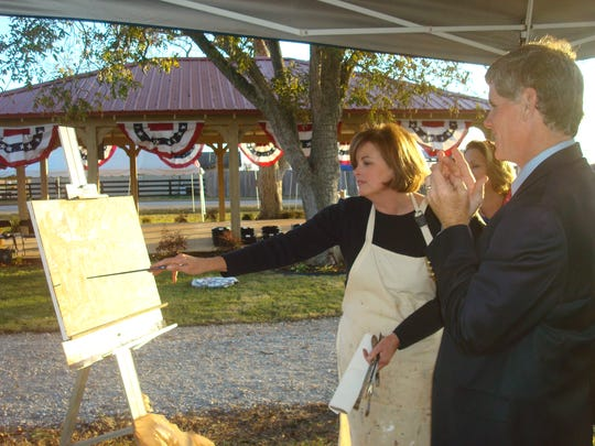 Local artist Barbara Davis stands next to the plein air painting she created during the 2012 Veterans Day program in the Town of Pike Road. Artists will again gather in Pike Road in October to paint outdoors.