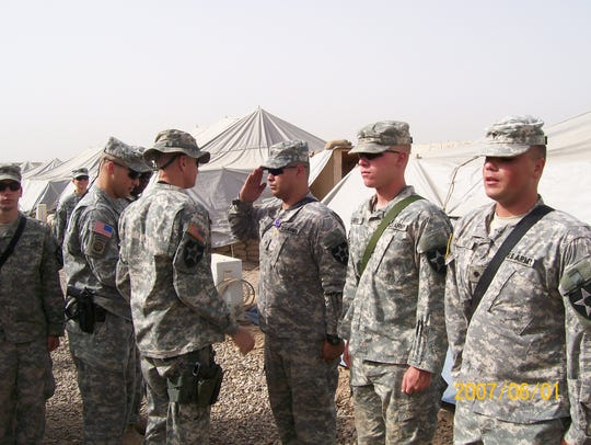 Lt. Col. Fred Johnson awards purple heart medals to