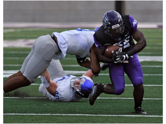 Abilene Christian University running back De'Andre Brown escapes the Houston Baptist defenders during Saturday's game against at Wildcat Stadium Sept. 16, 2017. ACU won, 24-3.