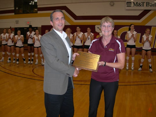 Former Salisbury University Athletic Director Michael Vienna presents volleyball coach Margie Knight with a plaque commemorating her milestone 400 wins.