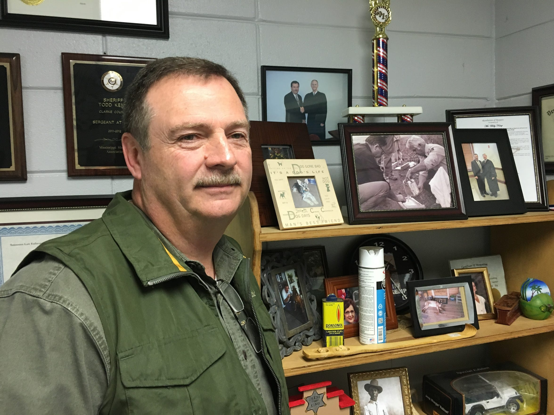 Clarke County Sheriff Todd Kemp stands in his office. A black-and-white photograph of his father, Billy Ray Kemp, longtime police chief for Quitman, can be seen on the top shelf.