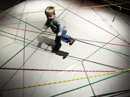 """A young child plays in the stretchy rope area inside the Kentucky Science Center's """"Science in Play"""" area."""