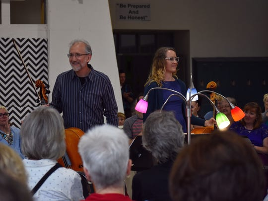 Joel Becktell and Lisa Donald, both Albuquerque cellists, smile as the crowd applauds them after a song.