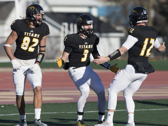 Craig Schommer (3) celebrates his third quarter touchdown with quarterback Brett Kasper (12) playing in the second round of the NCAA playoff game against Ohio Northern on Nov. 28 on J.J. Keller Field at Titan Stadium.