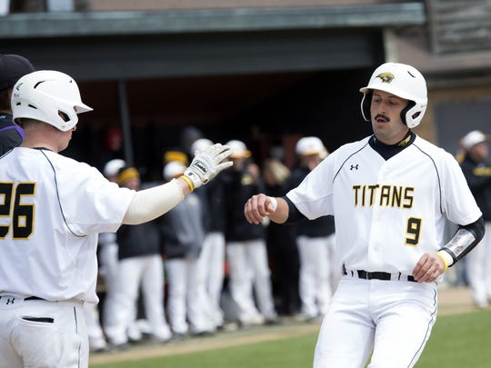 UW-Oshkosh's Tyler Kozlowski (9) is congratulated by Taylor Grimm after scoring a run in the first game of Sunday's doubleheader against UW-Stevens Point.