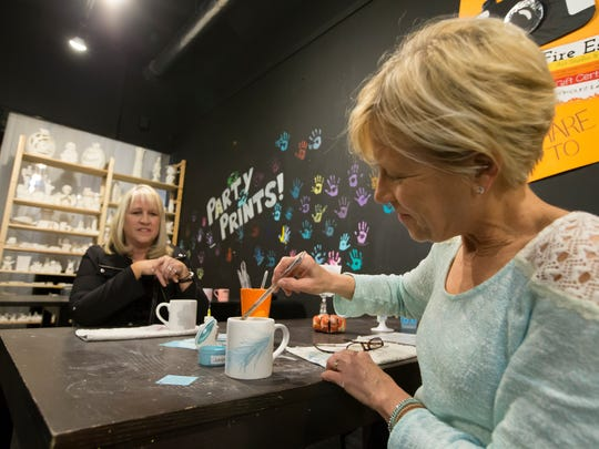 Natalie Klapa paints a coffee cup on Gallery Walk night