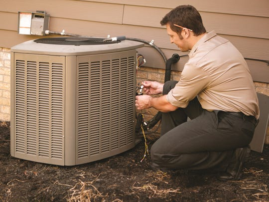 Certified technician working on an AC unit.