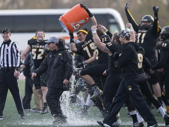 Pat Cerroni, head coach for UW-Oshkosh, gets dumped on by Sam Versnik after a big win over the UW-Eau Claire earning the WIAC Division 3 title on Saturday at Titan Stadium November 14, 2015.