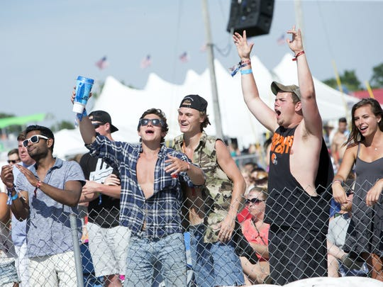 A group of friends roar as the band Locash plays at
