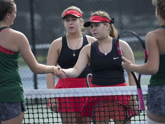 Hannah, left, and Amanda Dorsey, twin sisters in their senior year at Neenah High School, shake hands at the end of their match against Oshkosh North Thursday during the FVA Tennis Meet at Oshkosh North High School September 28, 2017.