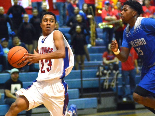 Las Cruces High's Marcus Scott breaks away from a Carlsbad High School defender on Friday night at LCHS Gym.