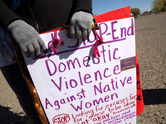 Ema Thompson holds a sign promoting an end to domestic violence Thursday outside the Shiprock Chapter house.
