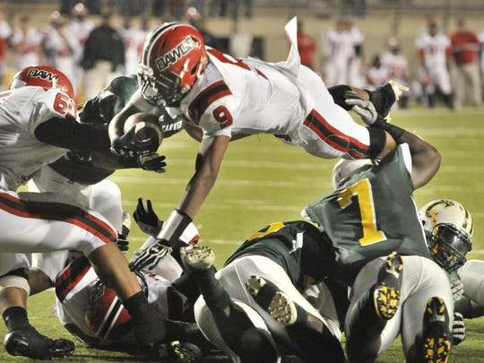 Opelika's Jakell Mitchell, top (9) jumps over Carver defenders on the way to a touchdown during their game at Cramton Bowl in Montgomery, Ala., on Friday, Nov. 30, 2012.