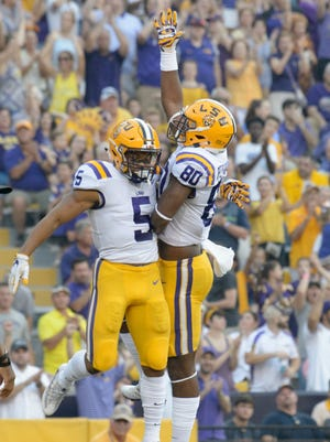 LSU running back Derrius Guice (5) scores a touchdown and celebrates with tight end Jamal Pettigrew (80) in an NCAA college football game against Syracuse in Baton Rouge, Saturday, Sept. 23, 2017.