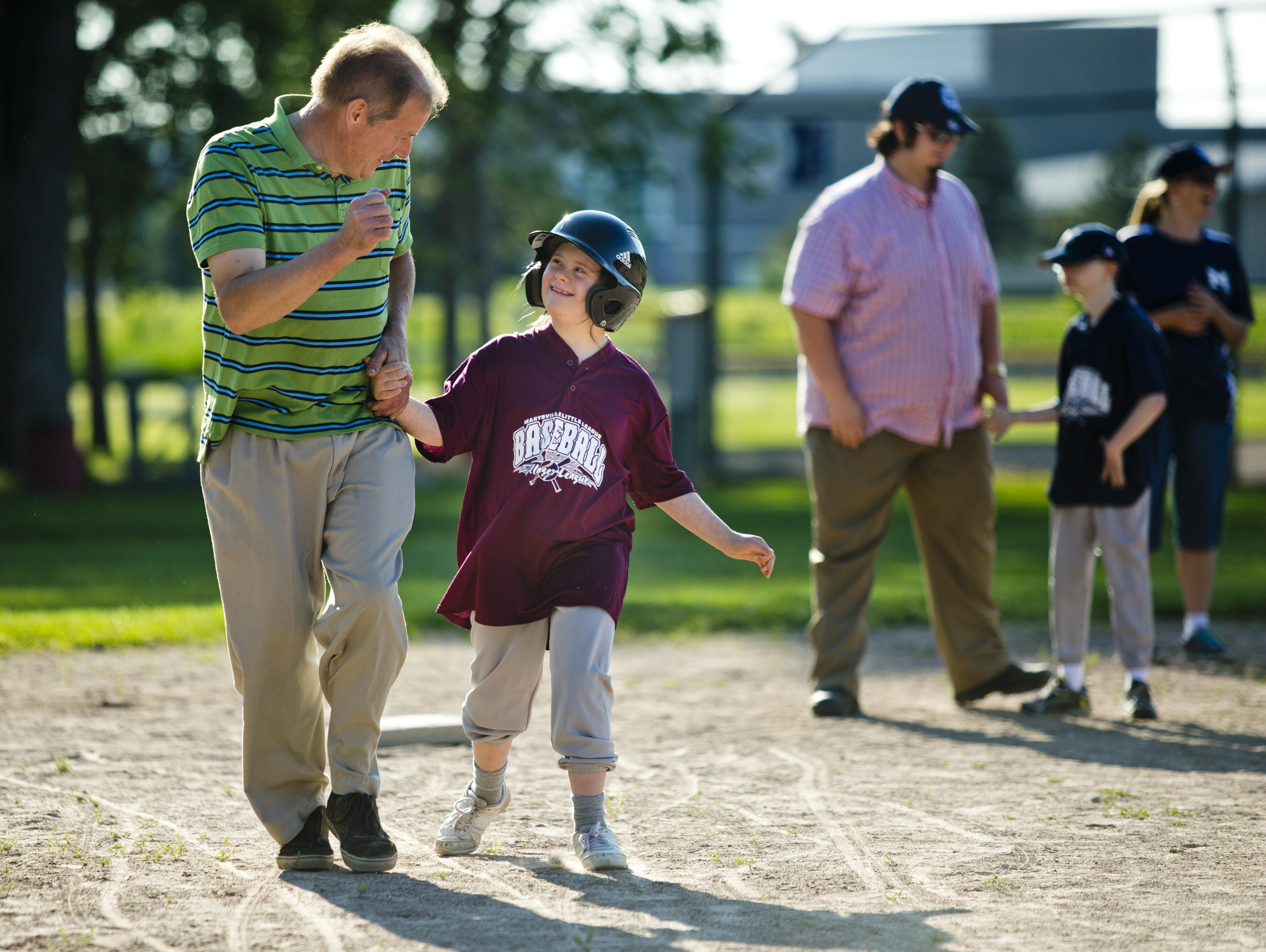Dan Rhein, of Port Huron, runs to home plate with his daughter Claire Rhein, 11, during a Marysville Little League Challenger Division baseball game Thursday, July 2, 2015 at Marysville Municipal Park.