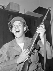 Mickey Lolich sports a new uniform in Detroit's police station on July 29, 1967 as he polishes the rifle he's carrying as a member of the Air National Guard. He was called up when civil unrest broke out in Detroit.
