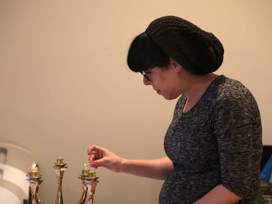 Elana Straus lights two Shabbat candles on a candelabra