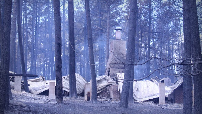 The remains of a Timberon home smolder Thursday. The fire destroyed or damaged about 44 residential structures, 16 vehicles, 14 recreational vehicles and burned one Timberon Volunteer Fire Department engine. A total of 70 structures have been destroyed or damaged during the fire.