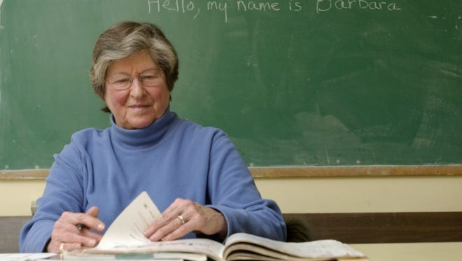 Barbara Snelling is pictured in 2004 as she volunteers her time to teach English as a second language at the Sara Holbrook Community Center in Burlington. At the beginning of each class, she writes her name on the chalkboard to assist her students who have trouble pronouncing her name.