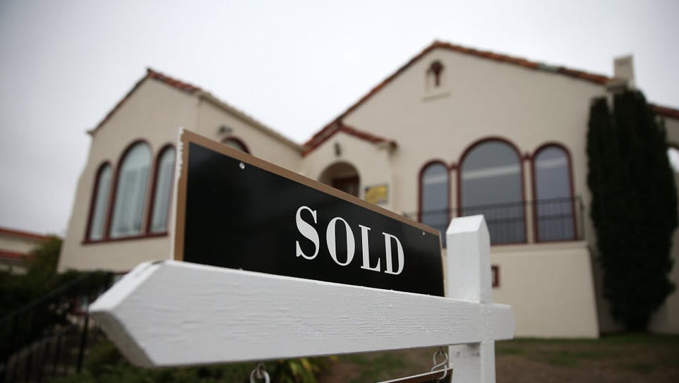A sold sign is posted in front of a home sale in San