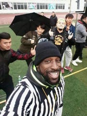 Wendell Brown poses with kids in China.