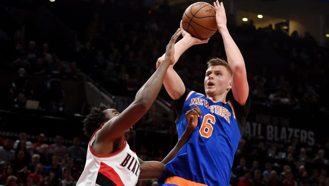 Knicks forward Kristaps Porzingis (6) shoots the ball over Portland Trail Blazers forward Al-Farouq Aminu (8) during the first half of the game at the Moda Center.