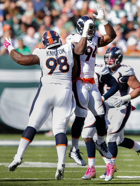 Denver Broncos defensive tackle Terrance Knighton (98) and defensive end DeMarcus Ware (94) celebrate after causing fumble against the New York Jets during the third quarter of an NFL football game, Sunday, Oct. 12, 2014, in East Rutherford, N.J. (AP Photo/Kathy Willens)