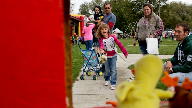 Kayleigh Richards, 7, of Fort Gratiot, plays a bean bag toss game with her family during the Port Huron Township Fall Festival Saturday, September 19, 2015 at Memorial Park.