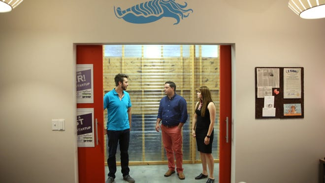 Nick Farrell, from left, Frank Valcarcel and Emily Morehouse of Cuttlesoft stand in the halls of DOMI Station, where they started their business. The company is a local standout tech startup that is now expanding to Denver, Colorado.