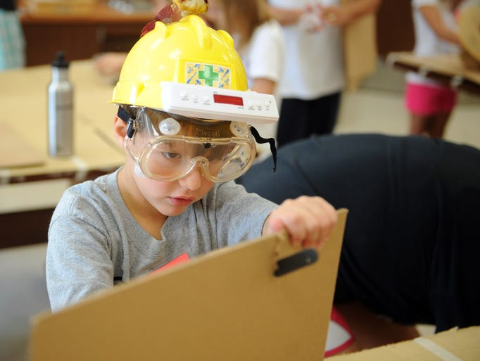 Kaleb Pitcher, 7, cuts cardboard while creating a pinball machine at Camp Invention at Coshocton Elementary School. Around 60 children took part in the week long camp.