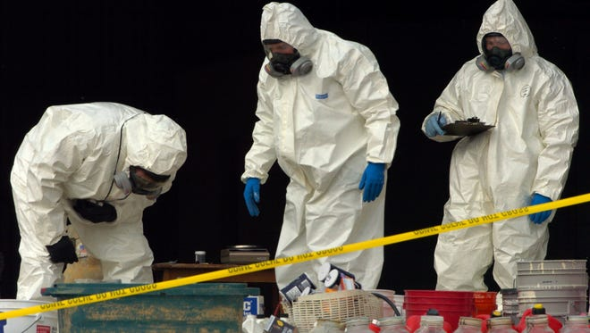 DEA investigators collect chemicals and other evidence at a methamphetamine lab recently.